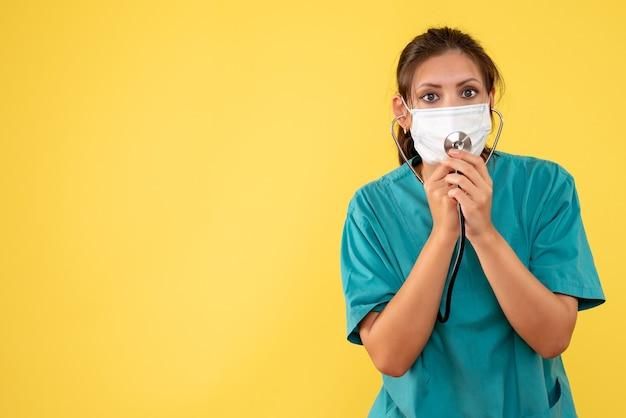 Vista frontal doctora en camisa médica y máscara con estetoscopio sobre fondo amarillo