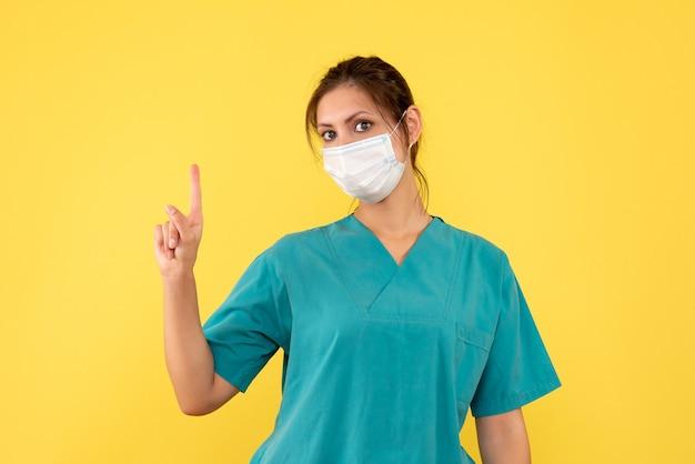 Vista frontal doctora en camisa médica y máscara sobre fondo amarillo