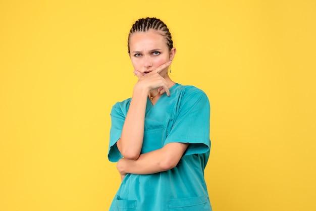 Vista frontal doctora en camisa médica posando y pensando, enfermera del hospital virus de salud de color covid-19