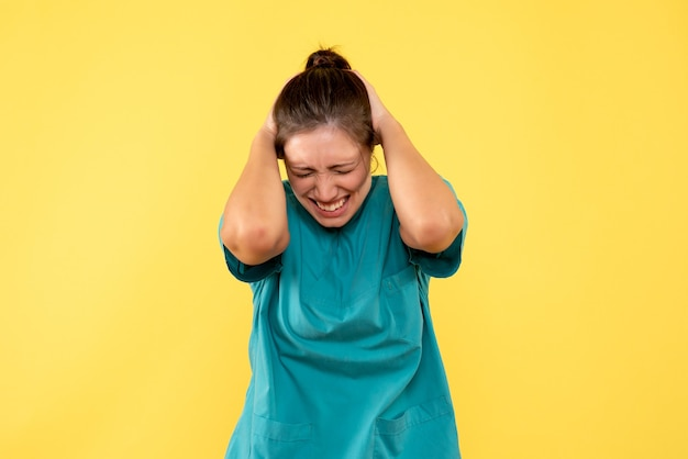 Vista frontal doctora en camisa médica sobre fondo amarillo