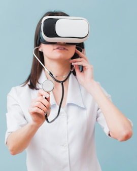 Vista frontal de la doctora con casco de realidad virtual y estetoscopio