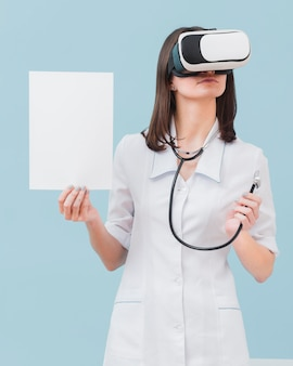Vista frontal de la doctora con casco de realidad virtual y papel en blanco
