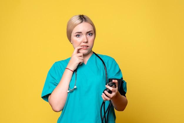 Vista frontal doctora comprobando su presión, enfermera del hospital médico de ambulancia de virus covid-19 de salud