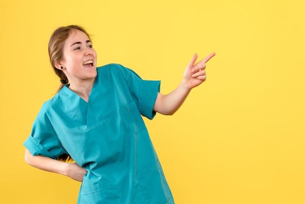 Vista frontal doctora emocionada sobre fondo amarillo salud hospital color virus