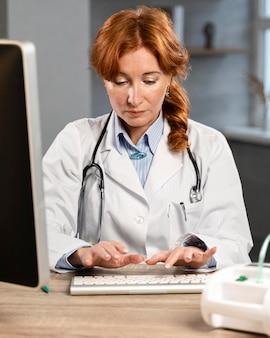 Vista frontal de la doctora escribiendo en la computadora en el escritorio