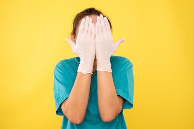 Vista frontal doctora en guantes blancos sobre fondo amarillo