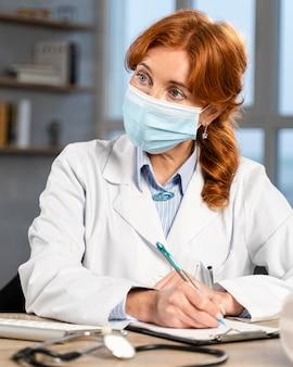 Vista frontal de la doctora con máscara médica en su escritorio escribiendo prescripción