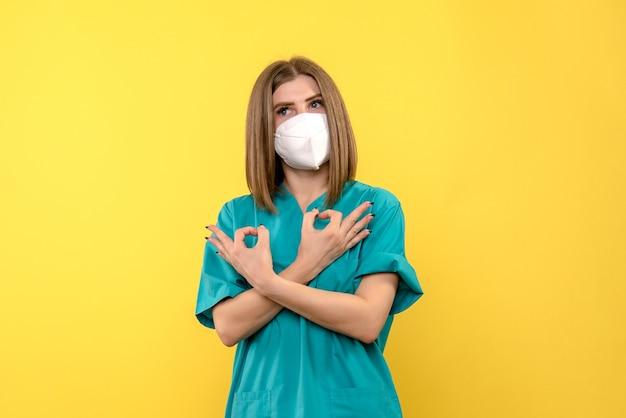 Vista frontal de la doctora con máscara en pared amarilla