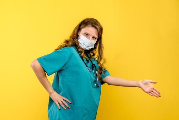 Vista frontal de la doctora en máscara en pared amarilla