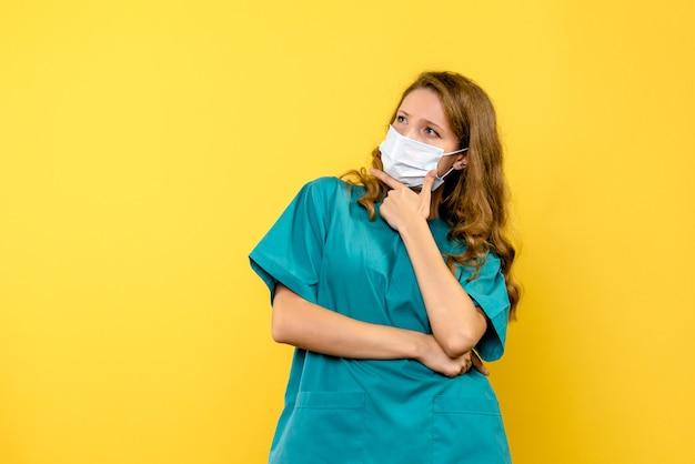 Vista frontal de la doctora en máscara sobre piso amarillo medic covid- virus pandémico