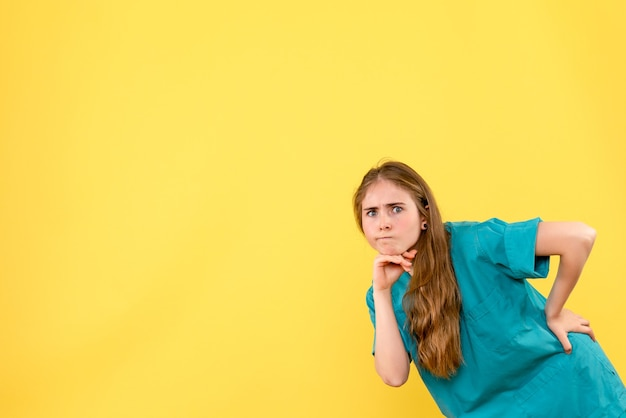Vista frontal doctora mirando sobre fondo amarillo salud médico emoción hospital