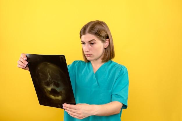 Vista frontal doctora mirando a través de rayos x en el espacio amarillo