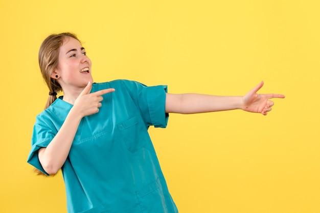 Vista frontal doctora regocijándose sobre fondo amarillo médico salud hospital emociones