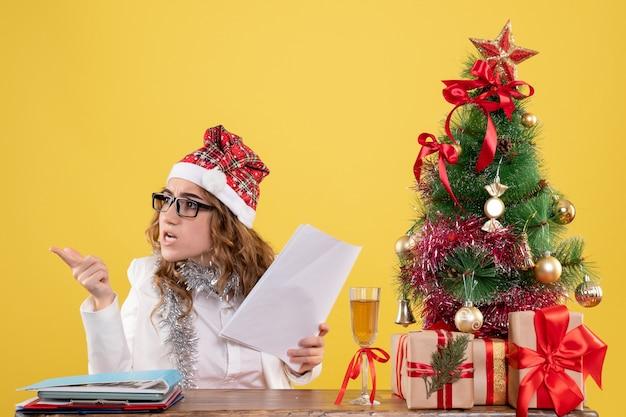 Vista frontal doctora sentada con árbol de regalos de navidad y sosteniendo documentos sobre fondo amarillo