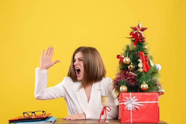 Vista frontal doctora sentada delante de la mesa sobre fondo amarillo con árbol de navidad y cajas de regalo