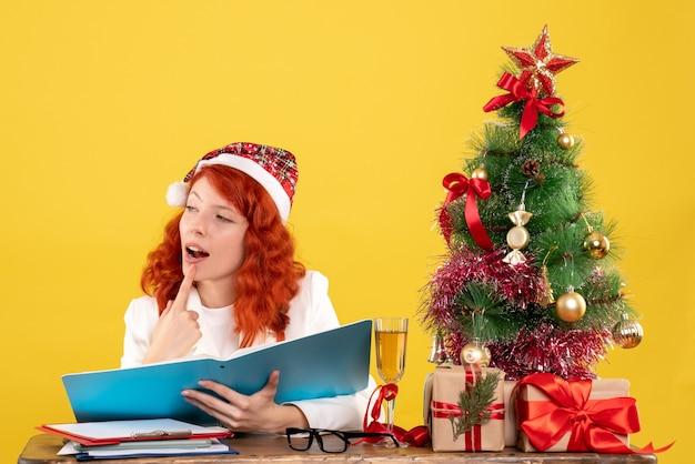 Vista frontal doctora sentada detrás de la mesa leyendo documentos sobre fondo amarillo con árbol de navidad y cajas de regalo