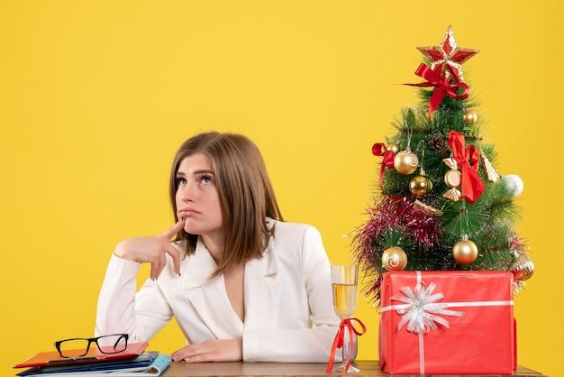 Vista frontal doctora sentada frente a su mesa pensando en fondo amarillo con árbol de navidad y cajas de regalo