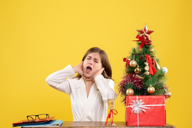 Vista frontal doctora sentada frente a su mesa sobre un fondo amarillo con árbol de navidad y cajas de regalo