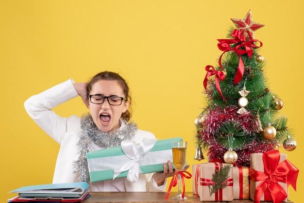 Vista frontal doctora sosteniendo regalo de navidad en paquete azul