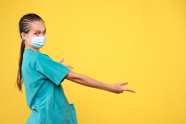 Vista frontal de la doctora en traje médico y máscara estéril en una pared amarilla