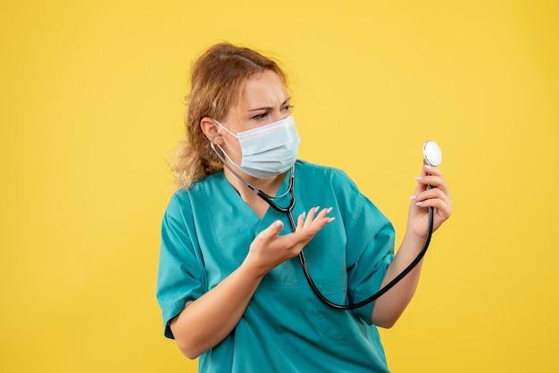 Vista frontal de la doctora en traje médico y máscara con estetoscopio en pared amarilla