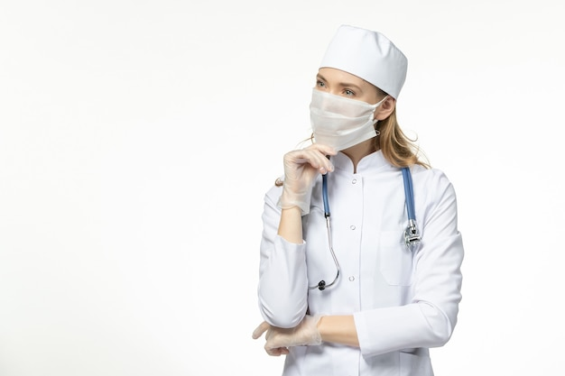 Vista frontal doctora en traje médico con máscara y guantes debido al coronavirus pensando en el covid-virus pandémico de la enfermedad de la pared blanca clara
