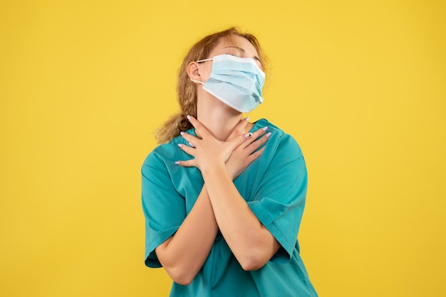 Vista frontal de la doctora en traje médico y máscara en la pared amarilla