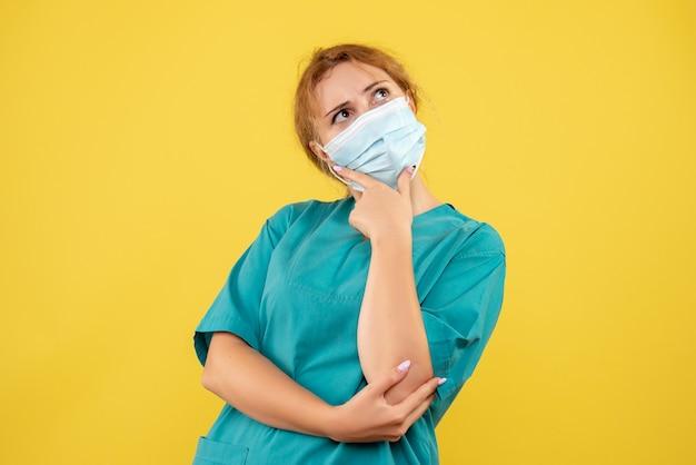 Vista frontal de la doctora en traje médico y máscara pensando en pared amarilla