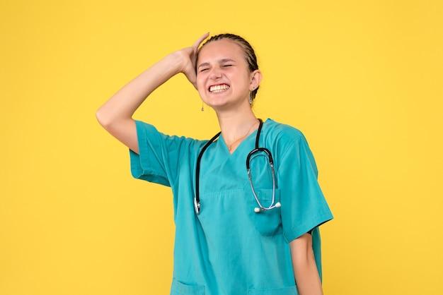 Vista frontal de la doctora en traje médico en pared amarilla
