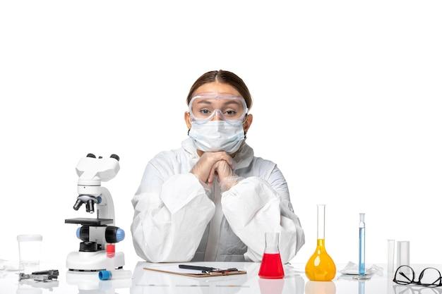Vista frontal de la doctora en traje de protección y con máscara sentada con soluciones sobre fondo blanco, medicina viral, salud covid
