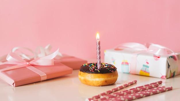 Vista frontal donut de cumpleaños con vela encendida
