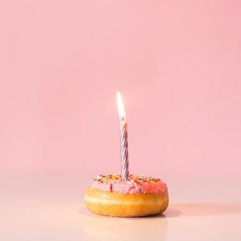 Vista frontal donut con vela encendida