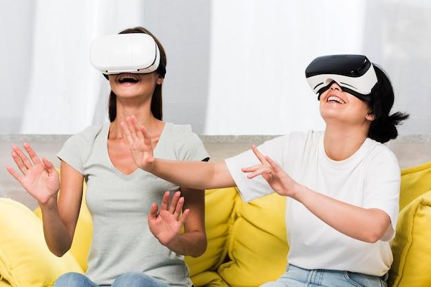 Vista frontal de dos amigos en casa con casco de realidad virtual