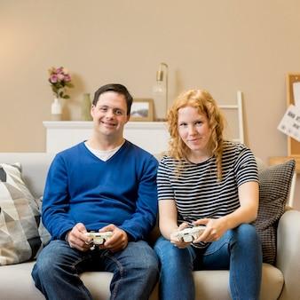 Vista frontal de dos amigos jugando videojuegos en casa
