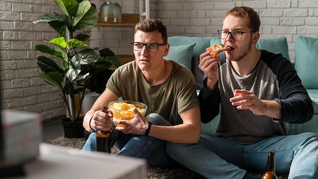 Vista frontal de dos amigos varones tomando cerveza con bocadillos y viendo deportes en la televisión