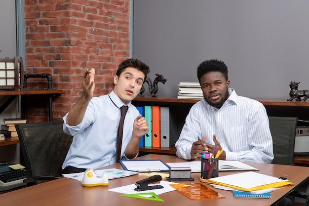 Vista frontal de dos apuestos empresarios sentados en el escritorio y mirando la presentación en la oficina