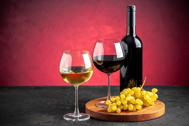 Vista frontal de dos copas de vino uvas amarillas sobre tablero de madera botella de vino sobre fondo rojo.