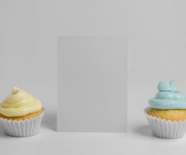 Vista frontal de dos cupcakes con tarjeta en blanco