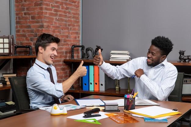 Vista frontal de dos empresarios dando pulgares