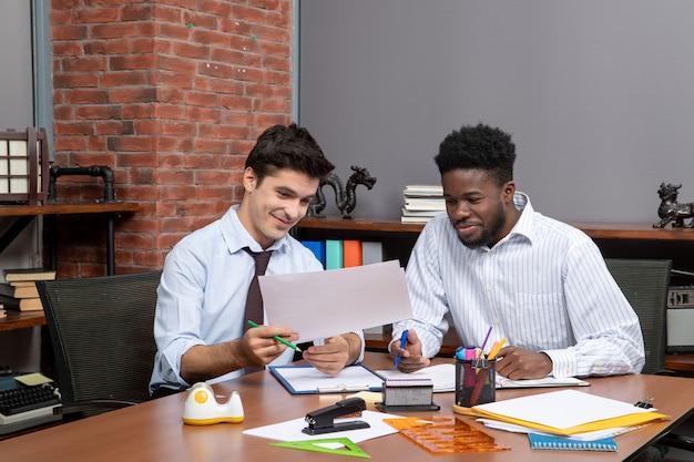 Vista frontal de dos empresarios ocupados que satisfacen trabajar juntos