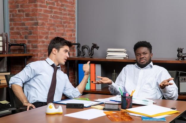 Vista frontal de dos gerentes de negocios que trabajan en la oficina