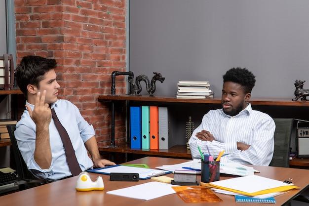 Vista frontal de dos gerentes de negocios sentados en el escritorio