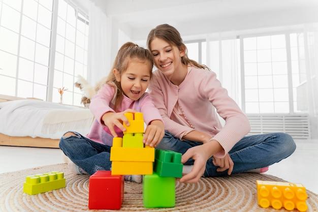 Vista frontal de dos hermanas jugando en casa con juguetes