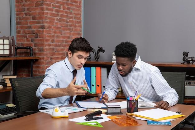 Vista frontal de dos hombres de negocios ocupados sentados frente al escritorio y discutiendo el proyecto en la oficina