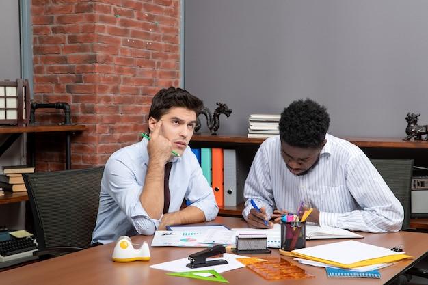 Vista frontal de dos hombres de negocios pensativos que trabajan juntos