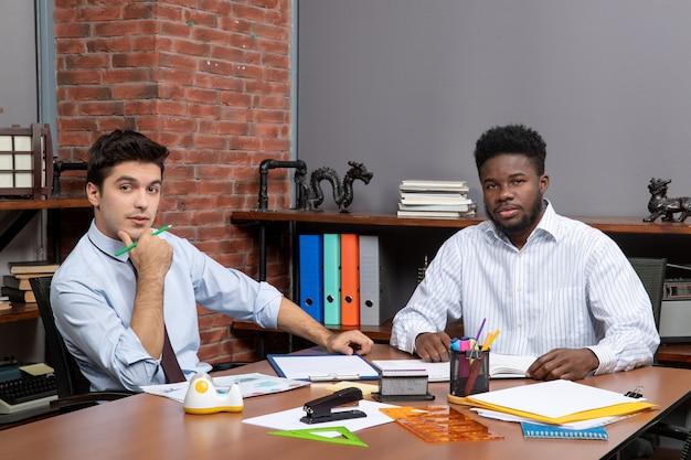 Vista frontal de dos hombres de negocios sentados frente al escritorio en la oficina