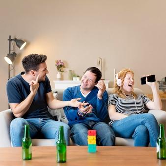 Vista frontal de dos hombres riéndose de mujer cantando