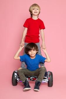 Una vista frontal dos muchachos en camisetas rojas y azules adorables lindas sonrientes montando en segway en el piso rosa