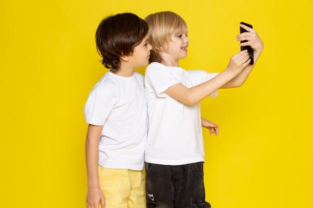 Vista frontal dos muchachos tomando selfie en camisetas blancas sobre piso amarillo