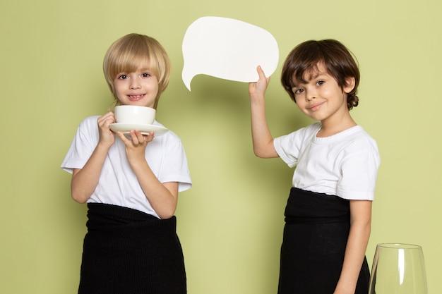 Una vista frontal dos niños sonriendo felices en camisetas blancas en el espacio de color piedra